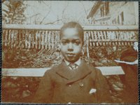 African-American boy in front of a picket fence