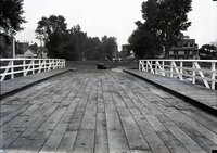 Bridge with wood surface, sidewalk and railings, (Wellington Street) Hartford, car and houses in background