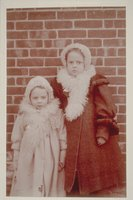 Ada Newbury of Mystic and another girl next to a brick wall