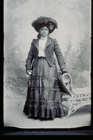 African American woman with feathered hat and purse