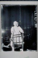 Ada Newbury of Mystic standing in high chair