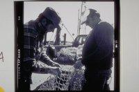 Al Maderia and John De Bragga mending nets, Stonington