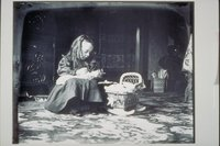 Ada Newbury of Mystic with doll and wicker doll cradle