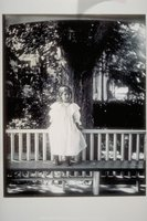 Young child standing on bench outside