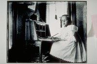 Ada Newbury of Mystic writing at a child's desk