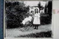 Ada Newbury, with a wicker doll carriage, in front of Newbury home, Willow and Church Streets, Mystic