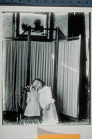 Ada Newbury of Mystic with doll in front of folding screen