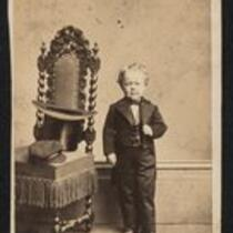 Photograph: George Washington Morrison Nutt (Commodore Nutt) standing beside a chair (owned by the Barnum Museum)